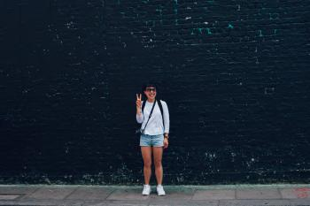 Woman in Blue Denim Shorts Standing in Front of Black Brick Wall