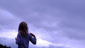 Woman in Blue Sweater Facing in Blue Clear Sky