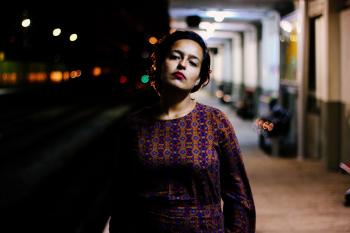 Woman in Brown and Purple Long-sleeved Shirt Standing Outside White Building during Nighttime