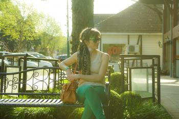 Woman in Brown Tank Top Sitting on Black Bench Beside Tree