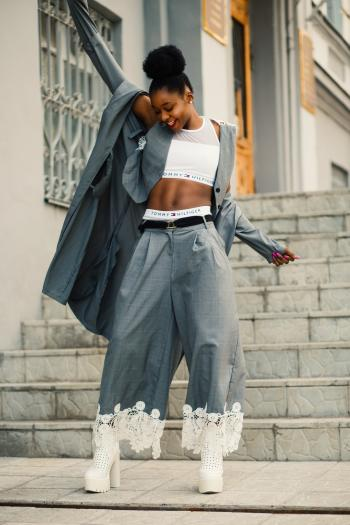 Woman in Gray Blazer Stands on Gray Concrete Floor