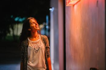 Woman in Gray Cardigan Standing Near Wall during Nighttime