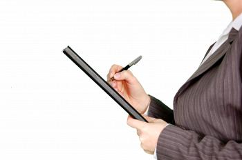 Woman in Gray Pinstripe Blazer Holding Black and Gray Stylus Pen and Black Pad