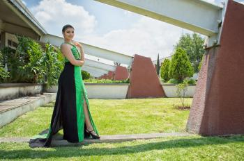 Woman in Green and Black Dress Standing in Front of Wall