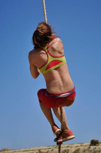 Woman in Green and Red Sports Bra Holding Rope during Daytime