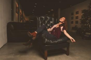 Woman in Maroon Scoop-neck Shirt Sitting on Black Leather Sofa Chair