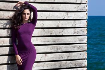 Woman in Purple Long Sleeve Dress Standing Beside White Wooden Wall