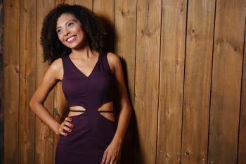 Woman in Purple V-neck Cutout Dress Leaning on Brown Wooden Wall