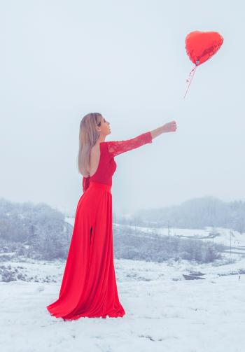 Woman in Red Floral Lace Long-sleeved Dress Standing With Red Heart Balloon