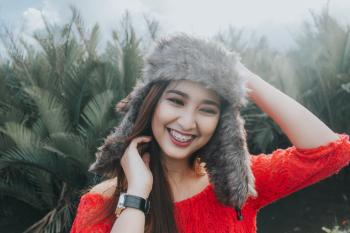 Woman In Red Off Shoulder Top Wearing Fur Beanie Smiling for Photo
