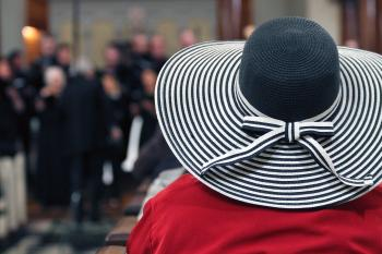 Woman in Red Shirt and Black and White Stripes Sunhat Surrounded by People