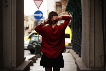 Woman in Red Sweater and Black Miniskirt Holding Hair Facing Road