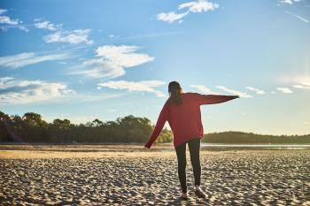 Woman in Red Sweater and Black Pants on White Sand Near Body of Water During Daytime