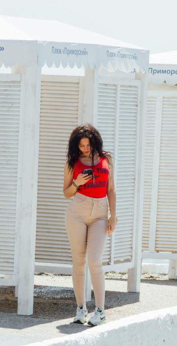 Woman in Red Tank Top and Gray High-waist Jeans Standing Near Wooden Cabinet