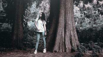 Woman in T Shirt Posing Beside Rough Bark Tall Tree in Grayscale Photography