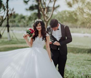 Woman in Wedding Dress Holding Flower With Man in Black Blazer
