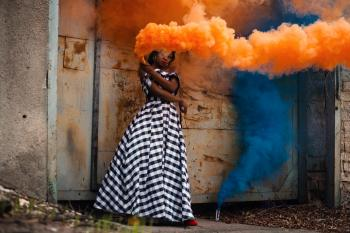 Woman in White and Black Dress Holding Orange Smoke