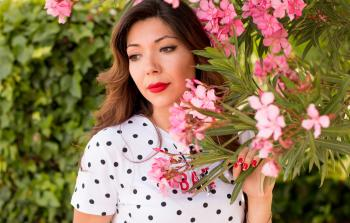 Woman in White and Black Polka Dots Dress Near Pink Flowers during Daylight