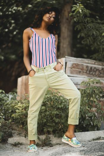 Woman in White and Black Stripe Spaghetti Strap Top and Beige Pants