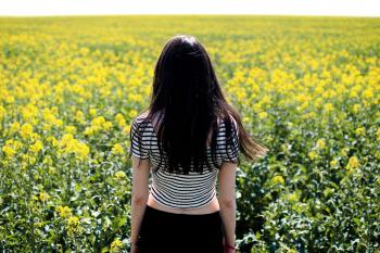 Woman in White and Black Striped Crop Top Facing Field