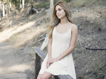 Woman in White Cami Dress Sitting on Gray Handrails during Daytime
