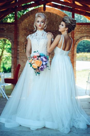 Woman in White Lace Wedding Dress Holding Flower Bouquet Beside Woman in White Dress