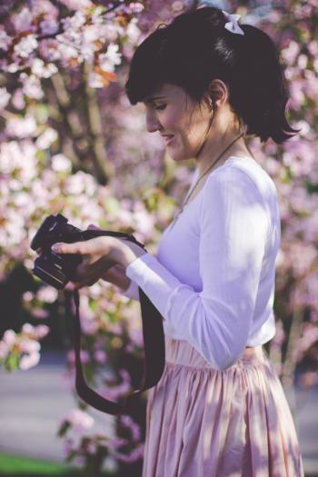 Woman in White Long Sleeve Top and Pink Skirt Holding Black Dslr Camera