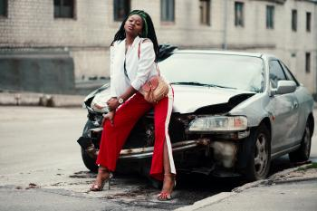 Woman in White Open Cardigan and Red and White Pants Sitting on Damage White Car