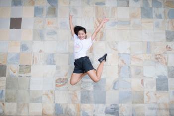 Woman in White Shirt and Black Shorts Taking Jump Shot Near Wall