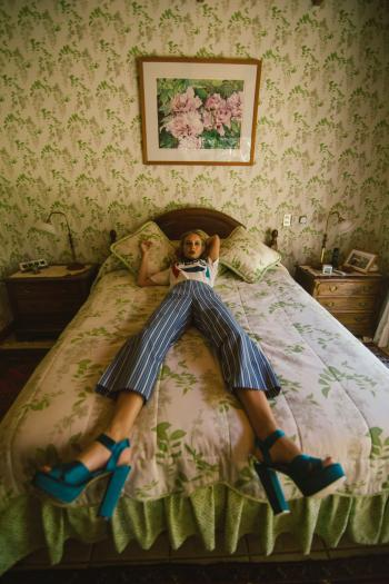 Woman in White Shirt Lying on White and Green Bed