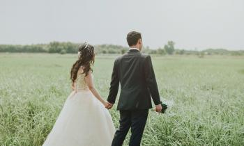Woman in White Wedding Dress Holding Hand to Man in Black Suit