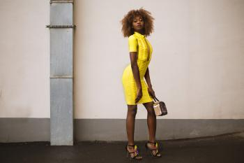 Woman in Yellow Knitted Dress Holding Beige Handbag