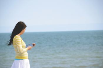 Woman In Yellow Long Sleeved Shirt And White Skirt Walking On Seashore