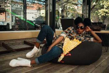 Woman Lying on Black Bean Bag Chair Near Cafe