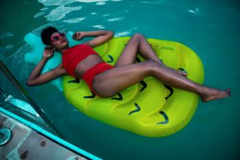 Woman Lying on Green Float Wearing Red Bikini