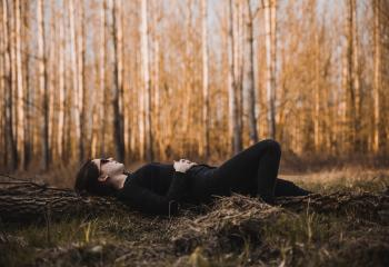 Woman Lying on the Ground Surrounded by Bare Trees