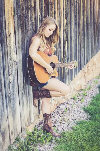 Woman Playing Guitar While Leaning on Wood during Daytime