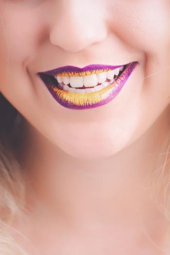 Woman Showing Her Purple and Yellow Lipsticks
