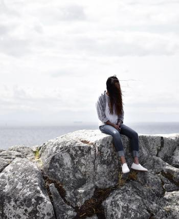 Woman Sits on Gray Rock