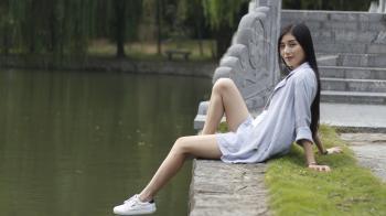 Woman Sitting beside a Lake