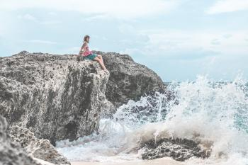Woman Sitting of Rock Near Body of Water