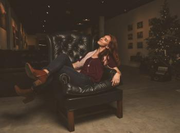 Woman Sitting on Black Leather Armchair