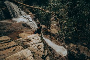 Woman Sitting on Edge Beside Flowing River