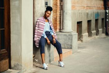 Woman Sitting on Gray Concrete Pillar