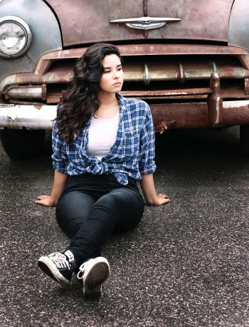 Woman Sitting on Gray Pavement Near Vintage Gray and Brown Car