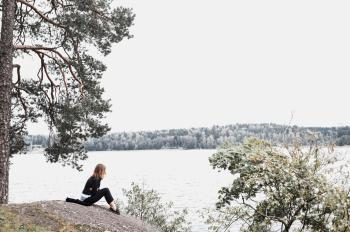 Woman Sitting on Gray Soil Near Body of Water