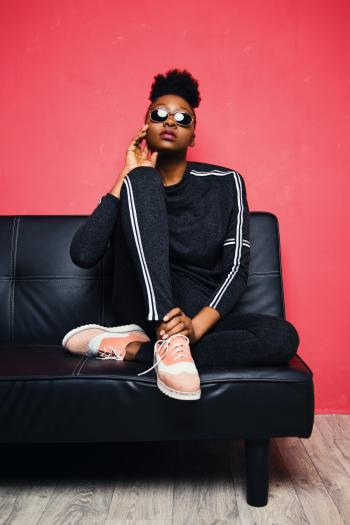 Woman Sitting on Sofa Bed Wearing Sunglasses