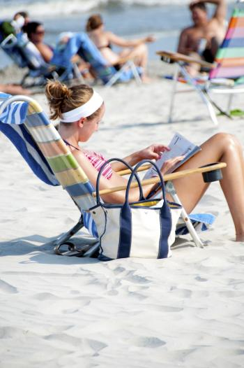 Woman Sitting on the Lounge Chair Reading Magazine on the Beach during Nighttime
