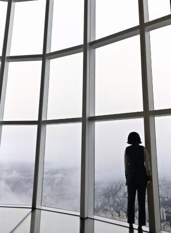 Woman Standing in Front of Glass Panel Inside Building