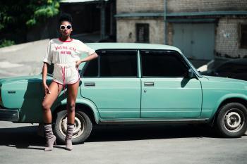 Woman Standing in Front of Teal Sedan